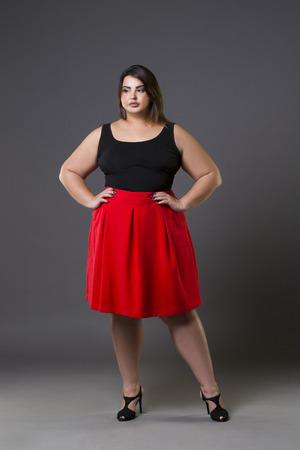 Plus-size fashion model in rode rok, dikke vrouw op grijze studio achtergrond, overgewicht vrouwelijk lichaam, volledige lengte portret