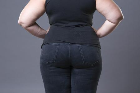 뚱뚱한 여성 엉덩이 청바지, 과체중 여자 몸 근접 촬영, 회색 스튜디오 배경