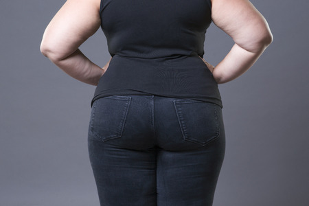 Fat female buttocks in blue jeans, overweight woman body closeup, gray studio background
