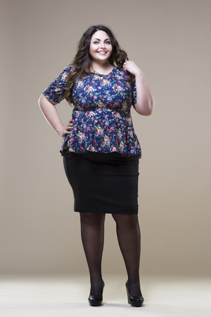 Happy plus size fashion model in casual clothes, fat woman on beige studio background, overweight female body, full length portrait Stock Photo