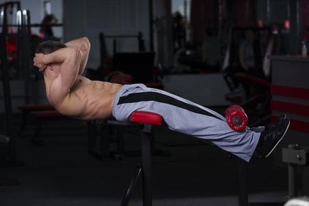 복부 벤치 체육관에서 운동을하는 남자, 완벽한 근육 질의 남성의 몸, 흑백 배경