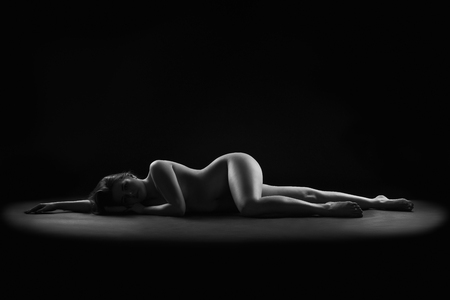 Art nude, perfect naked body, sexy woman on dark background, black and white photography, studio shot