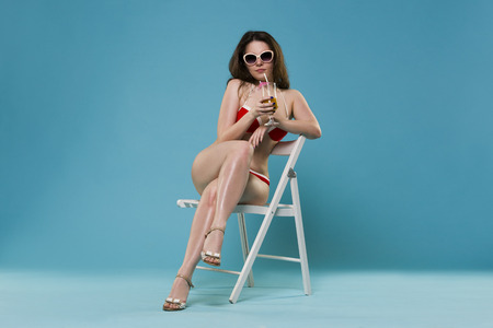 Beautiful young woman in red bikini with cocktail on blue background, studio shot