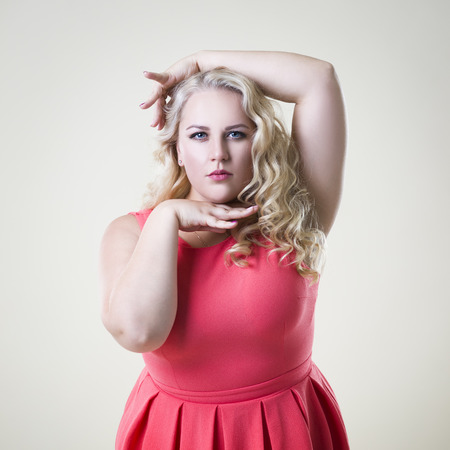 Plus size fashion model, fat woman on beige studio background, overweight female body Imagens
