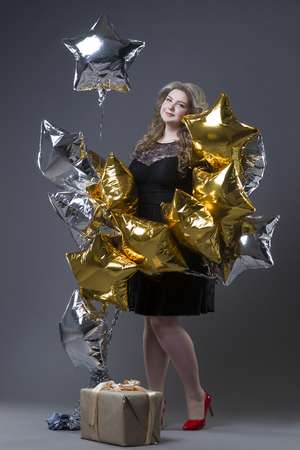 Plus size woman with gift box and balloons