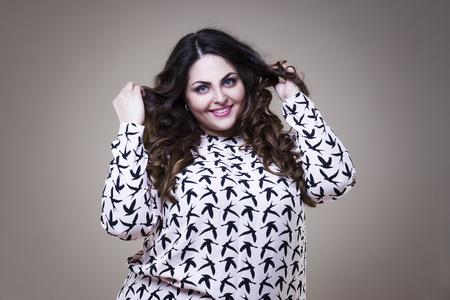 Happy plus size fashion model, fat woman on beige studio background, overweight female body Фото со стока