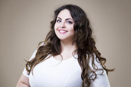 カジュアルな服のサイズのファッション モデル、ベージュのスタジオの背景、太りすぎの女性の身体の脂肪の女性プラス幸せ