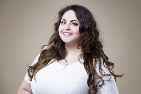 Happy plus size fashion model in casual clothes, fat woman on beige studio background, overweight female body