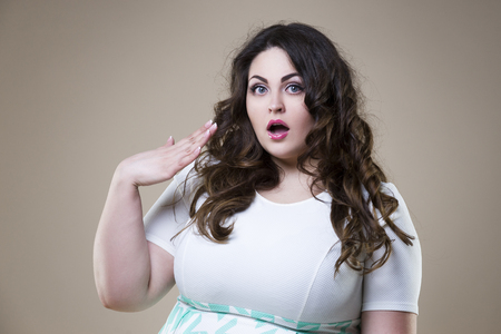 Surprised plus size fashion model, fat emotional woman on beige studio background, overweight female body