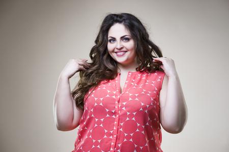 カジュアルな服でハッピープラスのサイズのファッションモデル、ベージュスタジオの背景に太った女性、太りすぎの女性の体