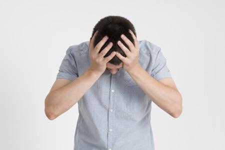 Hoofdpijn en migraine, man met hoofdpijn op grijze achtergrond, studio-opname Stockfoto