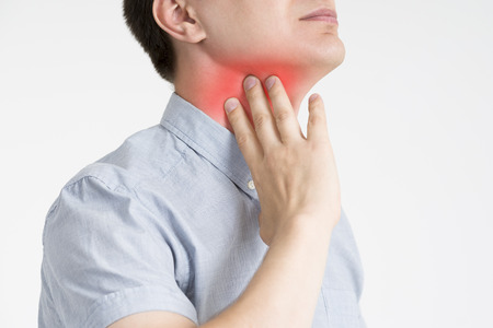 Keelpijn, mannen met pijn in de nek, grijze achtergrond, studio-opname Stockfoto - 88761590