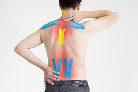 taping: Kinesio tape, kinesiology taping on human back, gray background