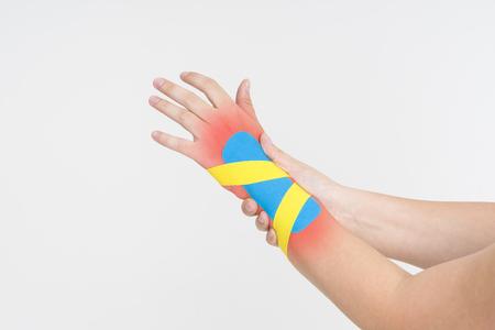 Kinesio tape, kinesiology taping on human hand, gray background