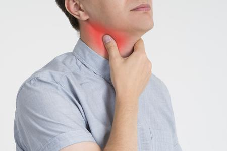 Sore throat, men with pain in neck, gray background, studio shot Stock Photo