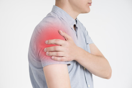Man with pain in shoulder on gray background, studio shot with red dot