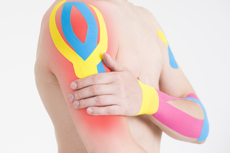 Kinesio tape, kinesiology taping on human hand, gray background