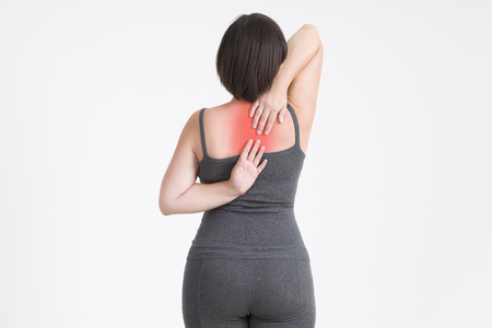 Neck pain, woman with backache on gray background with red dots Standard-Bild