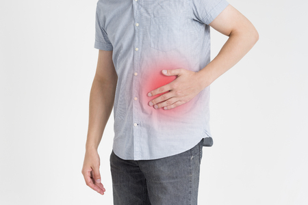 Man with abdominal pain, stomach ache on gray background, with red dot