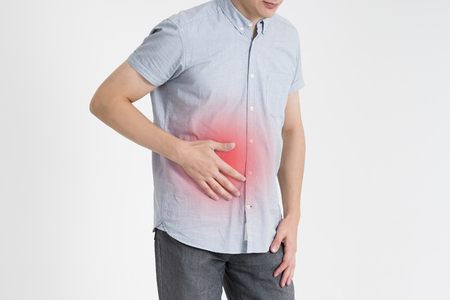 Man with abdominal pain, stomach ache on gray background, with red dot Stock Photo - 88768451