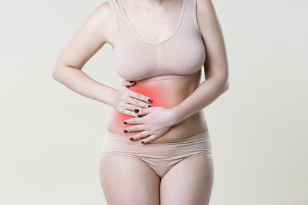 Appendicitis attack, woman with abdominal pain on beige background
