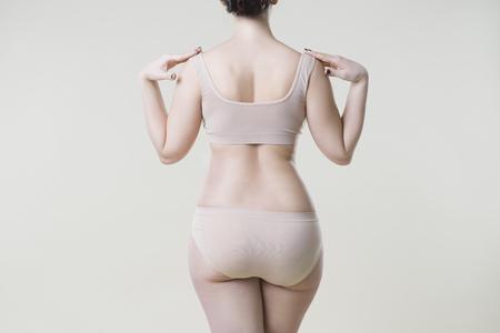 Woman in beige underwear on studio background, cellulite on female body, skin care concept