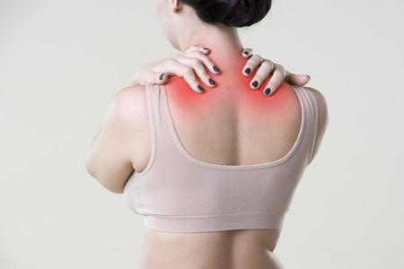 Neck pain, woman with backache on beige background, studio shot