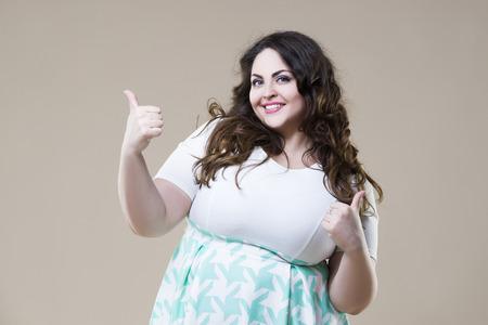 Modelo de moda feliz del tamaño extra grande en ropa casual, mujer gorda atractiva en fondo beige del estudio Foto de archivo - 90910188