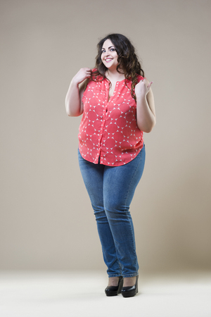 Happy plus size fashion model in casual clothes, sexy fat woman on beige studio background 스톡 콘텐츠