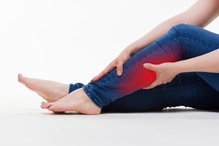 Pain in woman's legs, massage of female feet on white background, studio shot