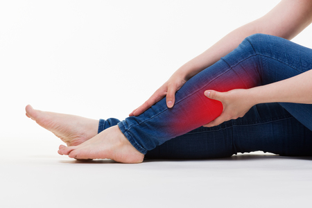 Pain in woman's legs, massage of female feet on white background, studio shot