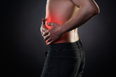 Man with abdominal pain, stomach ache on black background, with red dot Stock Photo