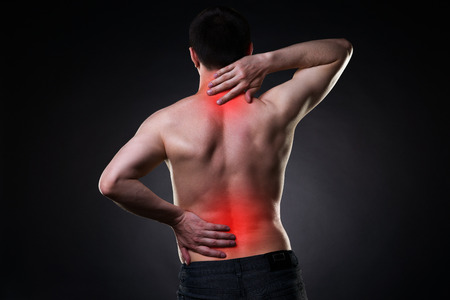 Back pain, man with backache on black background with red dots