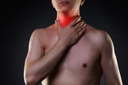 Sore throat, men with pain in neck, black background, studio shot Stock Photo
