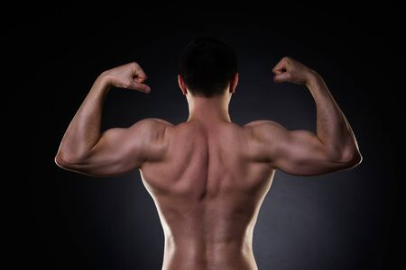 Handsome bodybuilder posing on black background, perfect muscular male back, studio shot Stock Photo