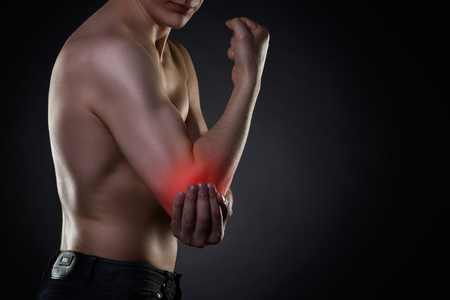 Pain in elbow, joint inflammation, studio shot with red dot on black background