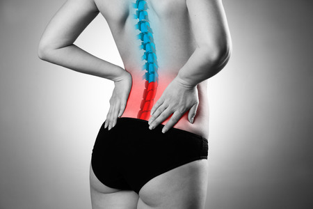 Pain in the spine, woman with backache, injury in the lower back, black and white photo with highlighted skeleton Stock Photo