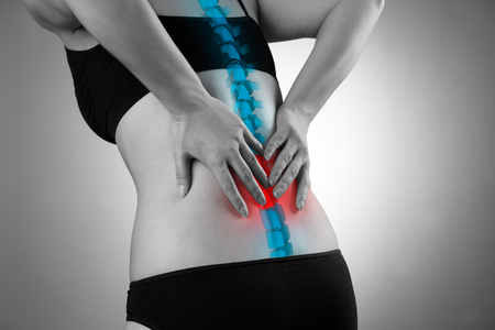 Pain in the spine, woman with backache, injury in the lower back, black and white photo with highlighted skeleton Stockfoto