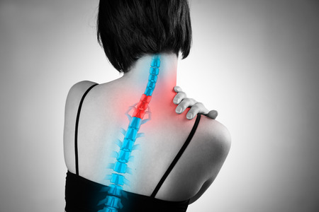 Pain in the spine, woman with backache, injury in the human back and neck, black and white photo with highlighted skeleton