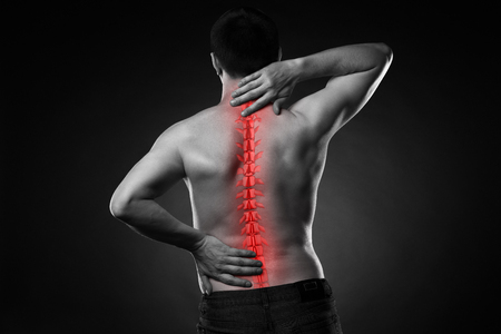 Pain in the spine, a man with backache, injury in the human back and neck, black and white photo with highlighted skeleton