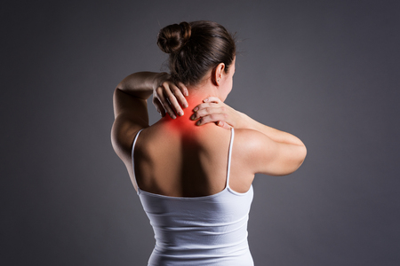 Neck pain, woman with backache on gray background, studio shot Stock Photo