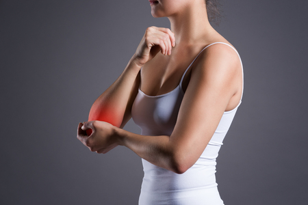 Woman with pain in elbow, joint inflammation on gray background Фото со стока