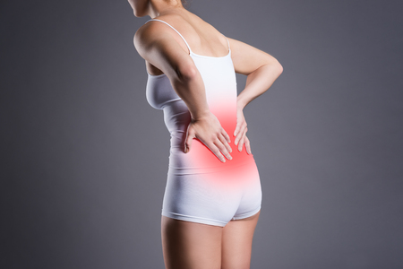 Back pain, kidney inflammation, ache in woman's body on gray background