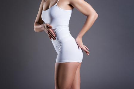 Slim woman in white underwear on gray studio background, perfect female body, body care concept