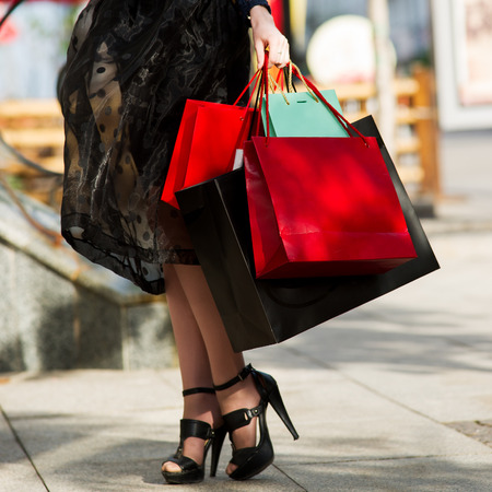 Woman with shopping bags walking in the city, holiday concert