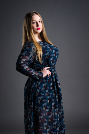 Plus size fashion model in long dress, fat woman on gray studio background, overweight female body, blonde hair and make-up 스톡 콘텐츠