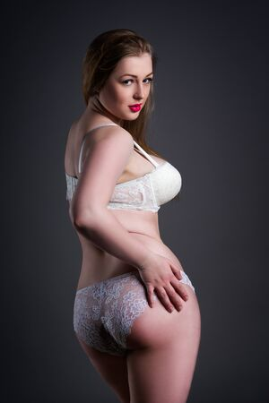 Plus size sexy model in white underwear, fat woman with big natural breast on gray studio background, overweight female body, blonde hair and make-up
