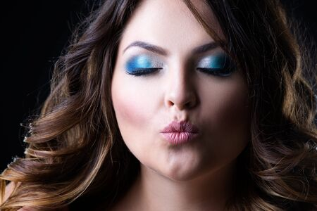 Plus size fashion model sends air kiss, beauty woman with professional makeup and hairstyle on black background, closeup studio shot