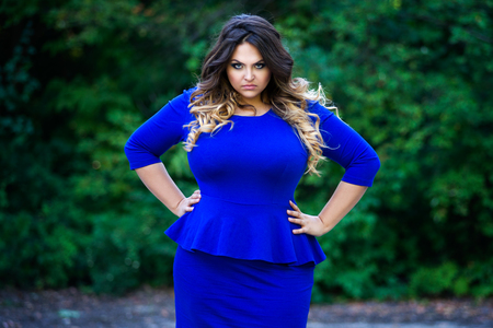 Angry plus size fashion model in blue dress outdoors, beauty woman with professional makeup and hairstyle on nature