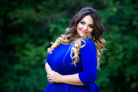 Happy plus size fashion model in blue dress outdoors, happiness beauty woman with professional makeup and hairstyle on nature